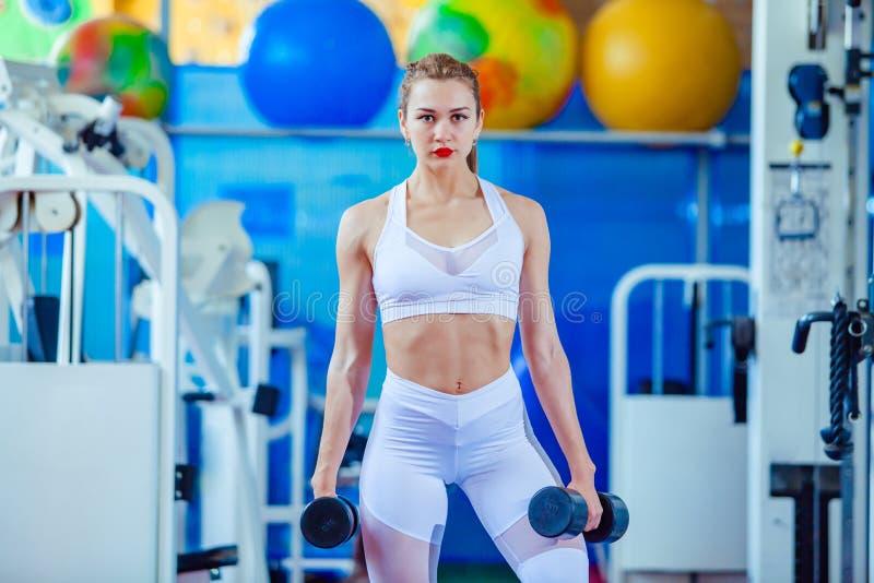 Ελκυστική νέα γυναίκα που επιλύει με τους αλτήρες σε μια γυμναστική στοκ εικόνα με δικαίωμα ελεύθερης χρήσης