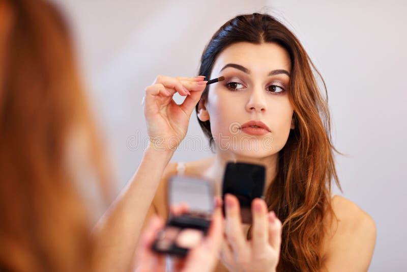 Ελκυστική νέα γυναίκα που κάνει τη σύνθεση εξετάζοντας τον καθρέφτη στο λουτρό στοκ φωτογραφία με δικαίωμα ελεύθερης χρήσης