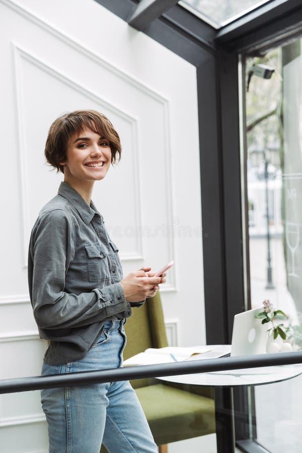 Ελκυστική νέα γυναίκα που στέκεται στον καφέ στο εσωτερικό στοκ φωτογραφίες
