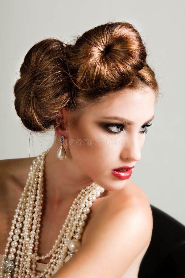 Ελκυστική νέα γυναίκα που φορά τα μαργαριτάρια στοκ εικόνες