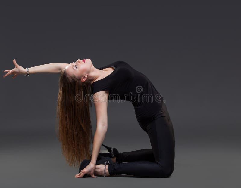 Ελκυστική νέα γυναίκα που χορεύει, σε ένα μαύρο υπόβαθρο στοκ φωτογραφία