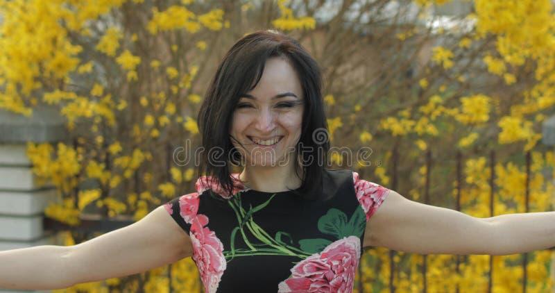 Ελκυστική νέα γυναίκα σε ένα φόρεμα με τα λουλούδια που κάνουν τα αστεία πρόσωπα στοκ φωτογραφία
