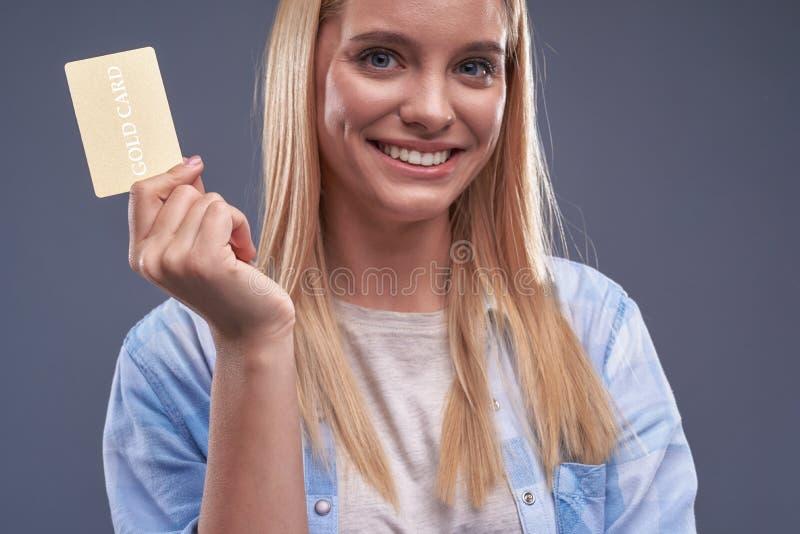 Ελκυστική νέα γυναίκα στο πουκάμισο που κρατά τη χρυσή κάρτα στοκ εικόνα με δικαίωμα ελεύθερης χρήσης