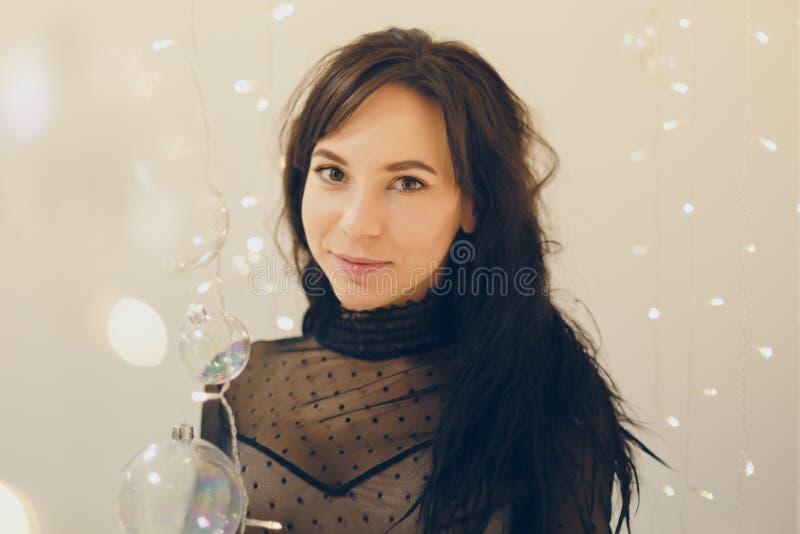 Ελκυστική νέα γυναίκα στο φόρεμα κοκτέιλ που μένει χαμογελώντας πέρα από το υπόβαθρο φω'των στοκ φωτογραφία