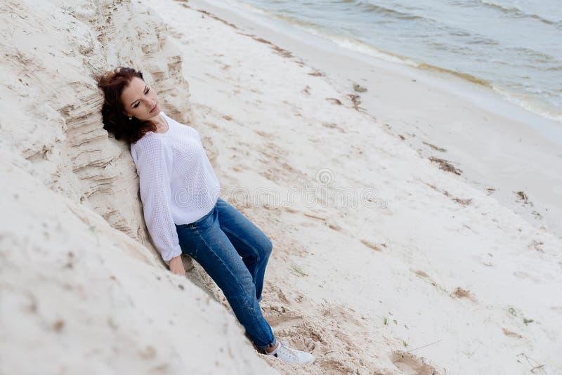 Ελκυστική νέα γυναίκα im θερμό ύφασμα στην παραλία στο κρύο καιρό στοκ φωτογραφίες με δικαίωμα ελεύθερης χρήσης