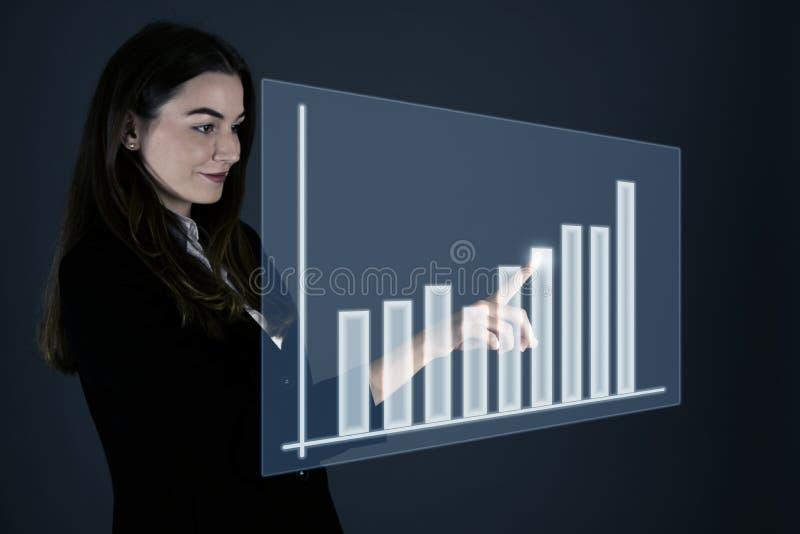 Ελκυστική νέα επιχειρησιακή γυναίκα που πιέζει το εικονικό κουμπί πέρα από το gra στοκ φωτογραφία