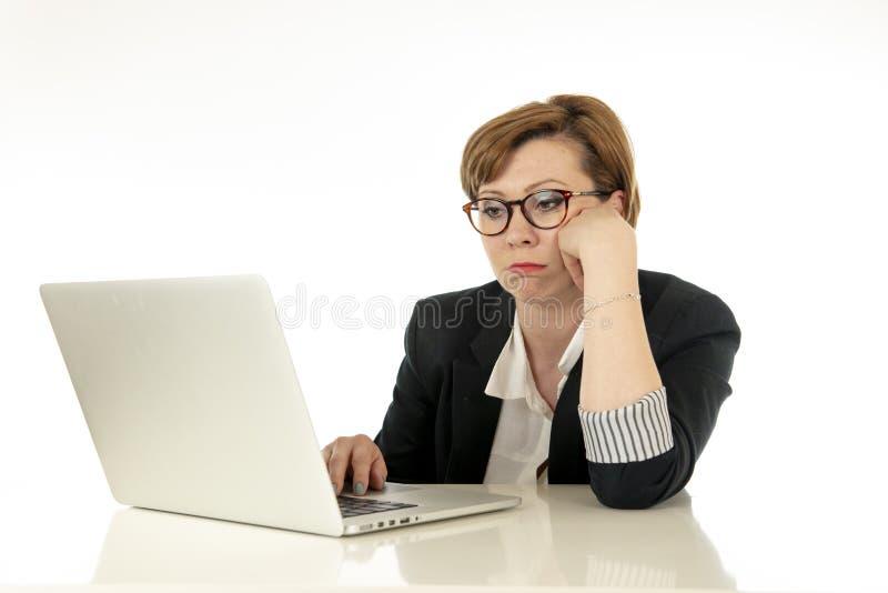 Ελκυστική νέα επιχειρησιακή γυναίκα στα γυαλιά που λειτουργούν στον υπολογιστή της που τονίζεται, που κουράζεται και που συντρίβε στοκ φωτογραφία