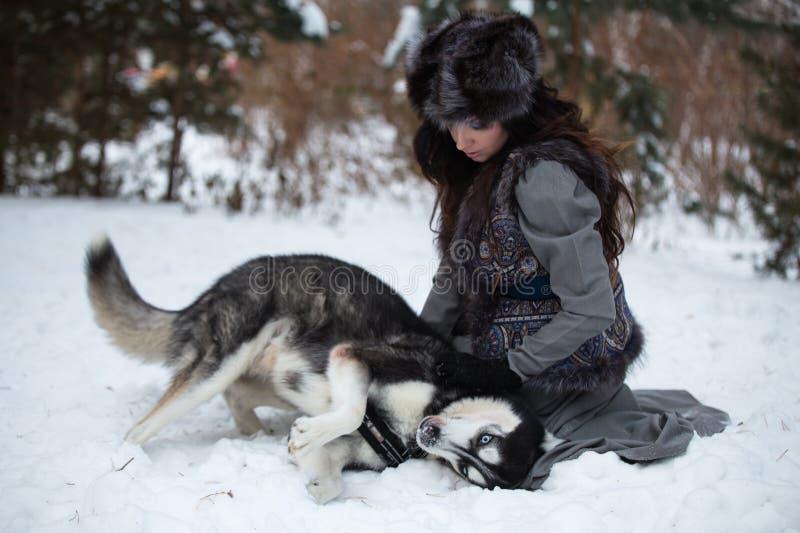 Ελκυστική νέα ευτυχής συνεδρίαση γυναικών και παιχνίδι με το γεροδεμένο σκυλί στοκ εικόνες