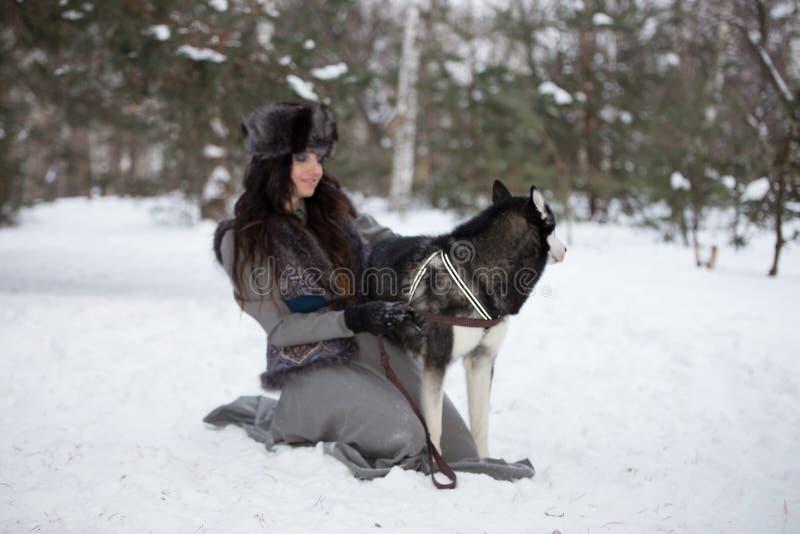 Ελκυστική νέα ευτυχής συνεδρίαση γυναικών και παιχνίδι με το γεροδεμένο σκυλί στοκ φωτογραφίες με δικαίωμα ελεύθερης χρήσης