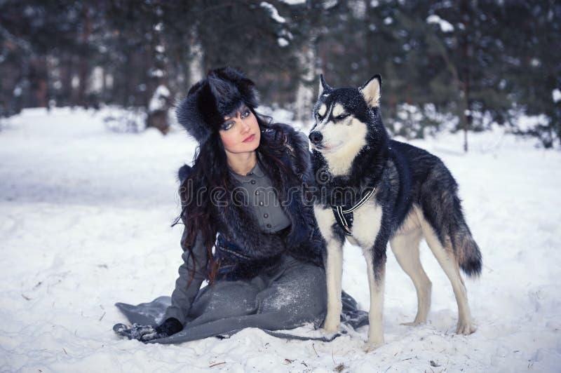 Ελκυστική νέα ευτυχής συνεδρίαση γυναικών και παιχνίδι με το γεροδεμένο σκυλί στοκ φωτογραφία