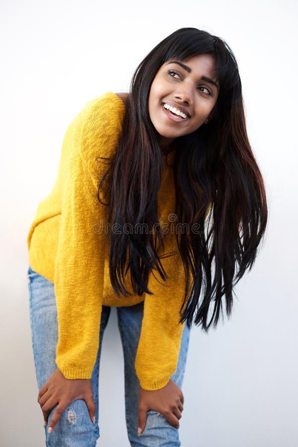Ελκυστική νέα ινδική γυναίκα που χαμογελά με τα χέρια στο γόνατο στο άσπρο κλίμα στοκ φωτογραφία