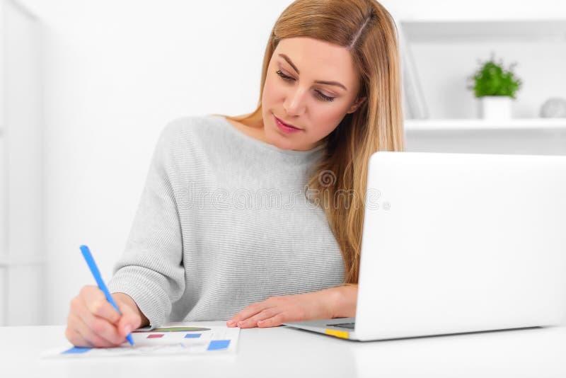 Ελκυστική νέα κυρία που εργάζεται με τη γραφική παράσταση στον πίνακα με το lap-top στοκ φωτογραφία
