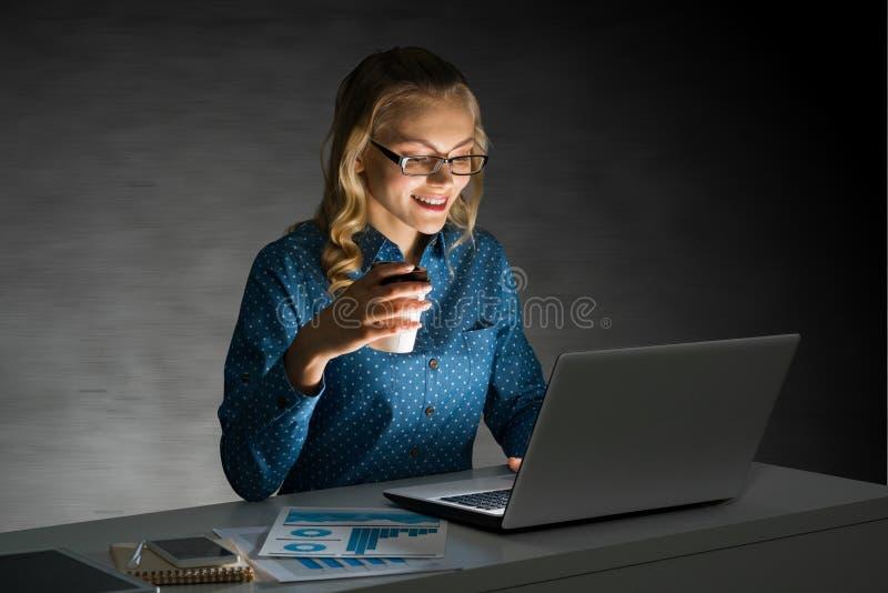 Ελκυστική ξανθή εργασία στο lap-top στο σκοτεινό γραφείο Μικτά μέσα στοκ εικόνες