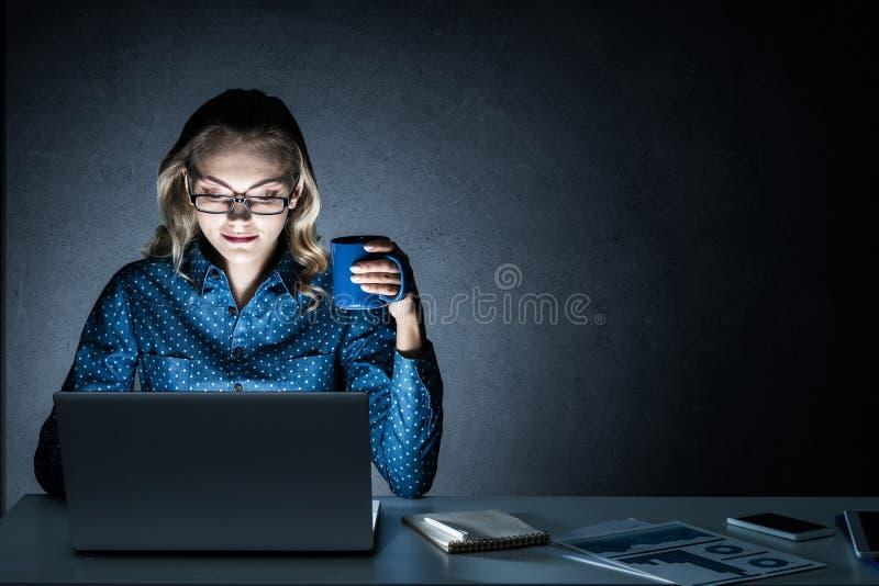 Ελκυστική ξανθή εργασία στο lap-top στο σκοτεινό γραφείο Μικτά μέσα στοκ εικόνες με δικαίωμα ελεύθερης χρήσης