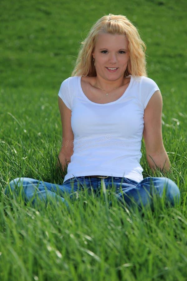 ελκυστική πράσινη γυναίκα συνεδρίασης λιβαδιών στοκ φωτογραφία