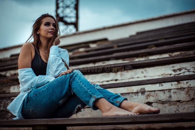 Ελκυστική συνεδρίαση γυναικών με τα γυμνά πόδια στο στάδιο Φορά ένα πουκάμισο και τα τζιν στοκ εικόνες με δικαίωμα ελεύθερης χρήσης