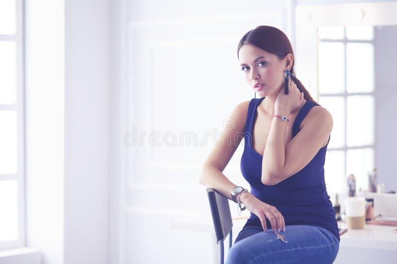 Ελκυστική συνεδρίαση γυναικών στην καρέκλα στο σαλόνι στοκ εικόνα