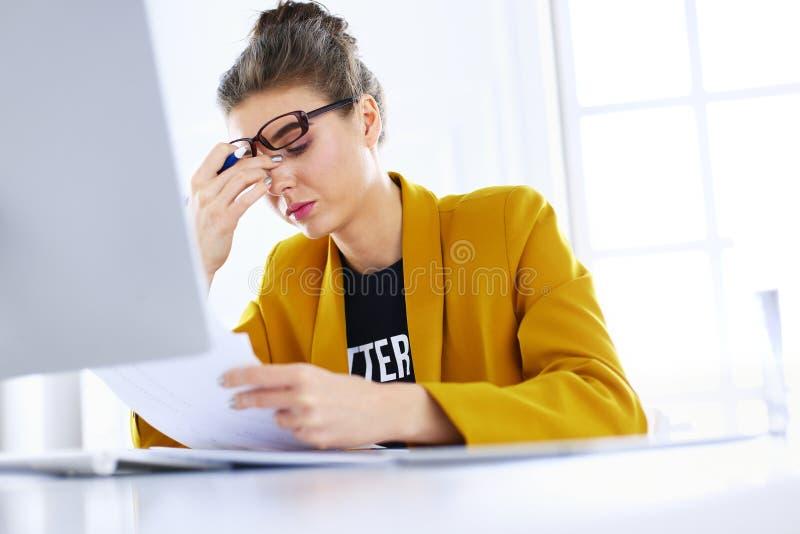 Ελκυστική συνεδρίαση γυναικών στο γραφείο στην αρχή, εργαζόμενος με το φορητό προσωπικό υπολογιστή, που κρατά το έγγραφο στοκ φωτογραφίες με δικαίωμα ελεύθερης χρήσης