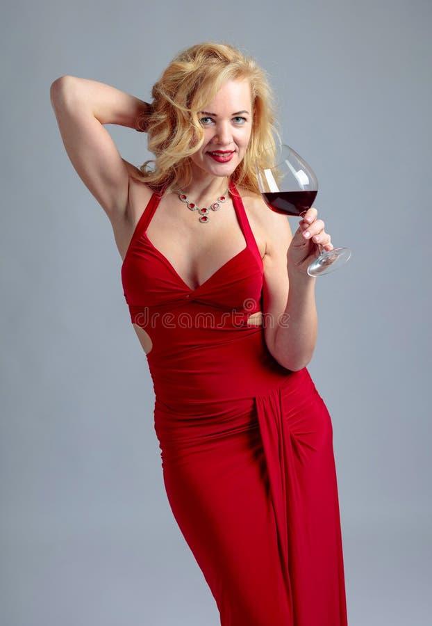 Ελκυστική χαμογελώντας ώριμη γυναίκα στο κόκκινο φόρεμα βραδιού με το ποτήρι του κόκκινου κρασιού στοκ εικόνες