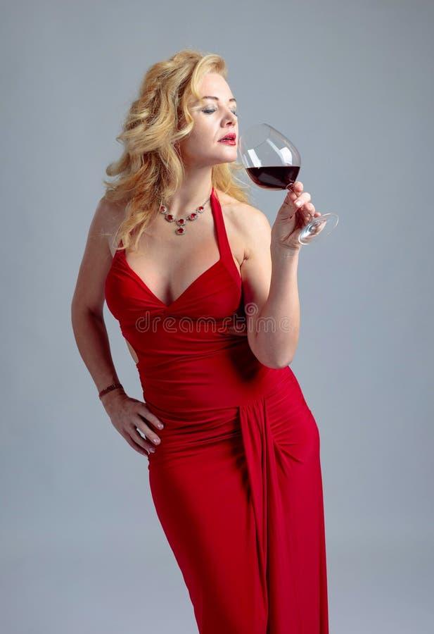 Ελκυστική χαμογελώντας ώριμη γυναίκα στο κόκκινο φόρεμα βραδιού με το ποτήρι του κόκκινου κρασιού στοκ φωτογραφία με δικαίωμα ελεύθερης χρήσης
