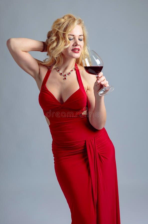 Ελκυστική χαμογελώντας ώριμη γυναίκα στο κόκκινο φόρεμα βραδιού με το ποτήρι του κόκκινου κρασιού στοκ εικόνες με δικαίωμα ελεύθερης χρήσης