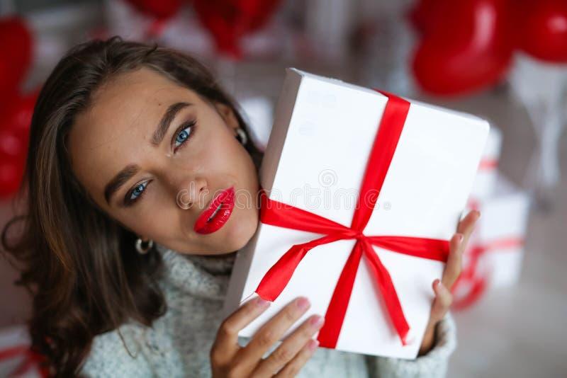 Ελκυστική όμορφη και προκλητική γυναίκα με το τέλειο χαμόγελο και τα δόντια Με το makeup στο δώρο εκμετάλλευσης γενεθλίων ή ημέρα στοκ φωτογραφίες