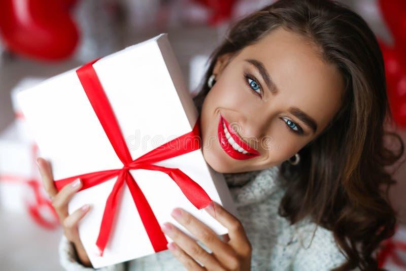 Ελκυστική όμορφη και προκλητική γυναίκα με το τέλειο χαμόγελο και τα δόντια Με το makeup στο δώρο εκμετάλλευσης γενεθλίων ή ημέρα στοκ εικόνα