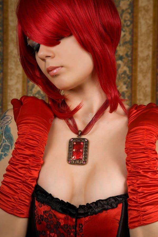 Ελκυστική redhead γυναίκα στον κόκκινο κορσέ στοκ εικόνα