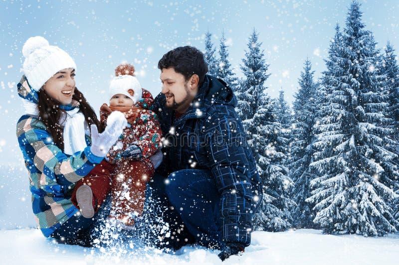 Ελκυστικοί άνδρας, γυναίκα και παιδί σε ένα υπόβαθρο ενός τοπίου Χριστουγέννων στοκ φωτογραφίες