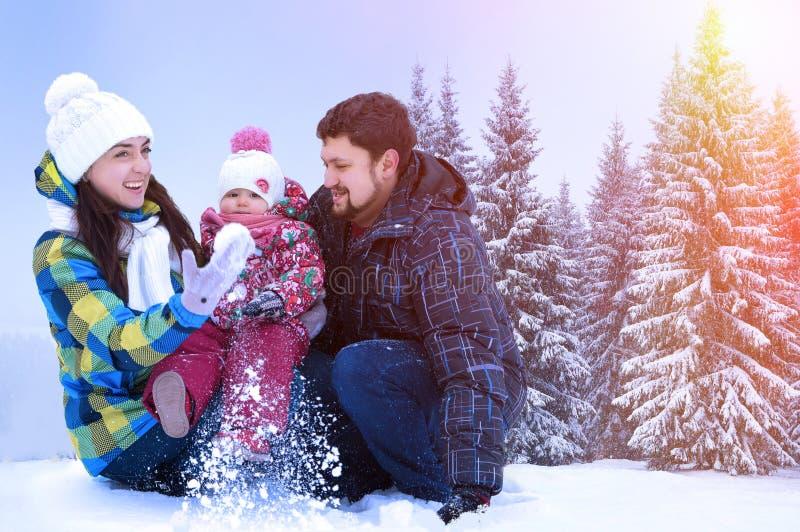 Ελκυστικοί άνδρας, γυναίκα και παιδί σε ένα υπόβαθρο ενός τοπίου Χριστουγέννων στοκ εικόνα με δικαίωμα ελεύθερης χρήσης