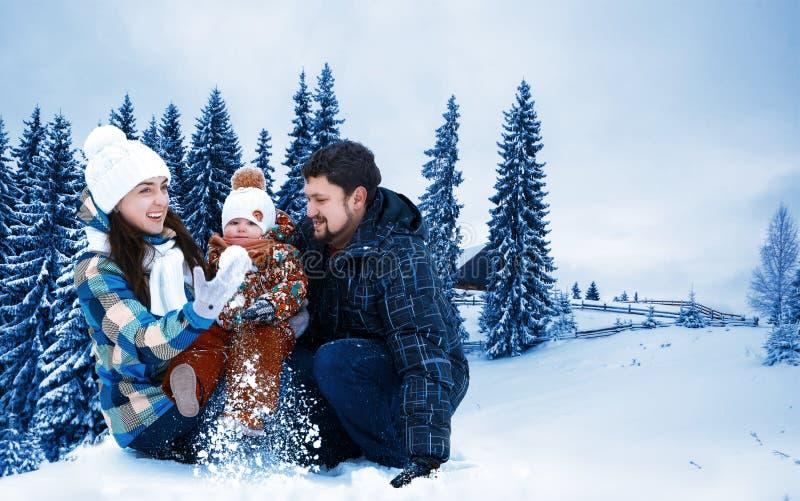 Ελκυστικοί άνδρας, γυναίκα και παιδί σε ένα υπόβαθρο ενός τοπίου Χριστουγέννων στοκ φωτογραφία με δικαίωμα ελεύθερης χρήσης