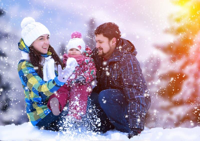 Ελκυστικοί άνδρας, γυναίκα και παιδί σε ένα υπόβαθρο ενός τοπίου Χριστουγέννων στοκ εικόνες