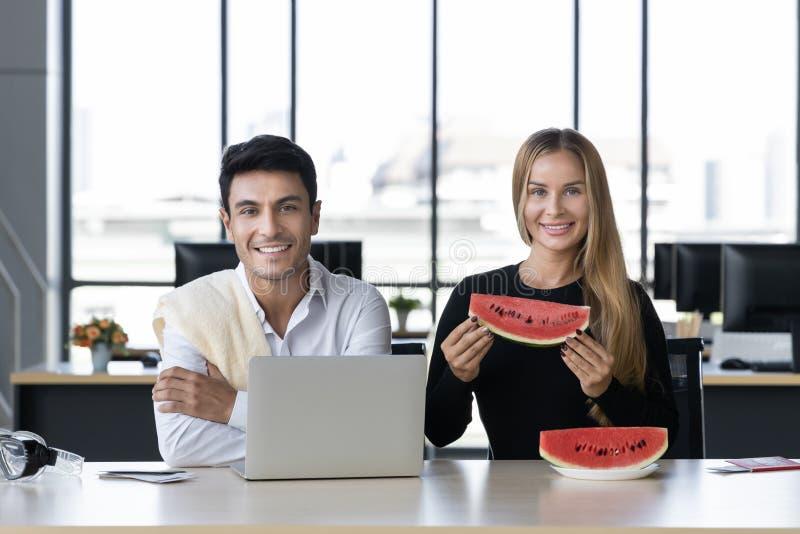 Ελκυστικοί καυκάσιοι επιχειρηματίες που τρώνε το καρπούζι στην αρχή Έννοια θερινών διακοπών στοκ φωτογραφίες με δικαίωμα ελεύθερης χρήσης