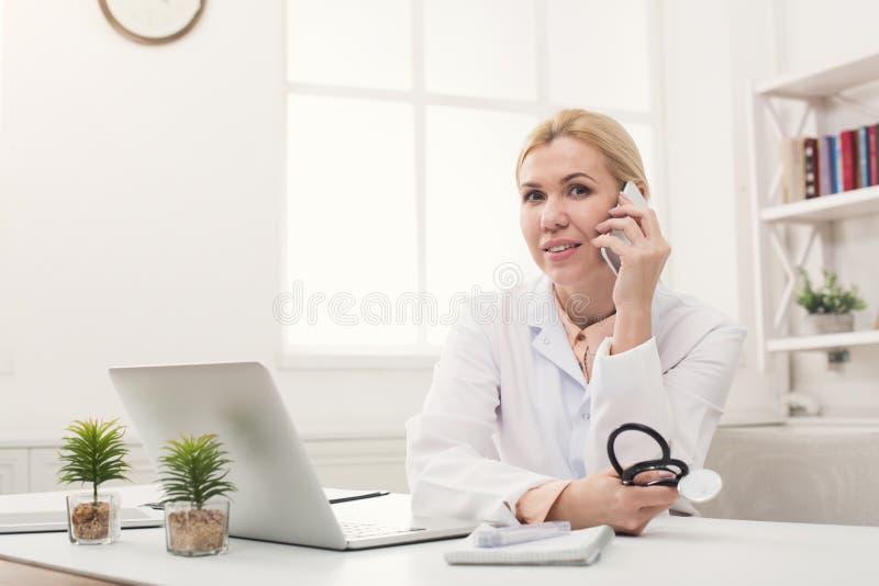 Ελκυστικός γιατρός που μιλά στο τηλέφωνο με τον ασθενή στοκ φωτογραφία με δικαίωμα ελεύθερης χρήσης