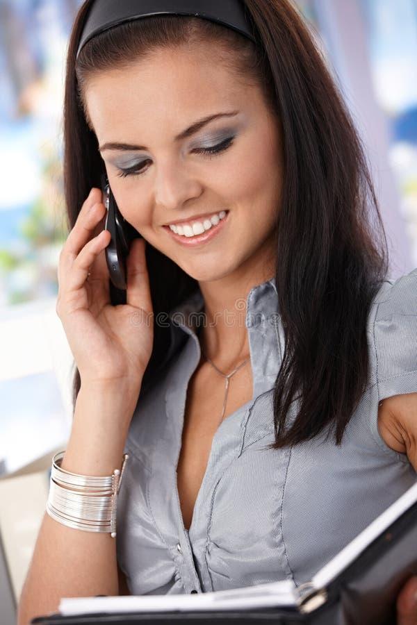 Ελκυστικός γραμματέας στο κινητό χαμόγελο στοκ φωτογραφία