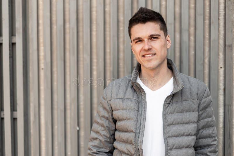 Ελκυστικός εύθυμος νεαρός άνδρας με ένα χαριτωμένο χαμόγελο με ένα μοντέρνο hairstyle σε μια μοντέρνη άσπρη μπλούζα στοκ φωτογραφίες με δικαίωμα ελεύθερης χρήσης