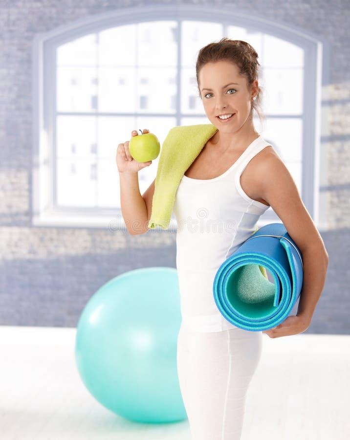 Ελκυστικός θηλυκός έχοντας το μήλο μετά από το workout στοκ εικόνα με δικαίωμα ελεύθερης χρήσης
