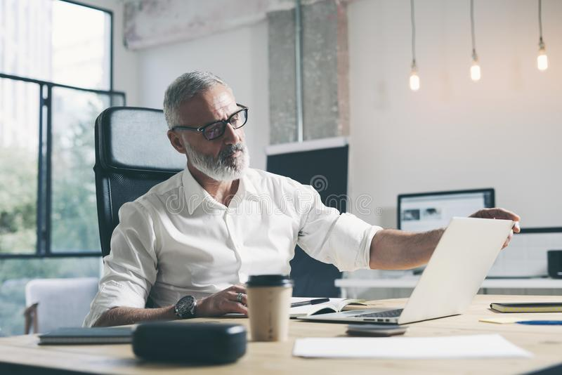 Ελκυστικός και εμπιστευτικός ενήλικος επιχειρηματίας που χρησιμοποιεί τον κινητό φορητό προσωπικό υπολογιστή εργαζόμενος στον ξύλ στοκ φωτογραφίες με δικαίωμα ελεύθερης χρήσης