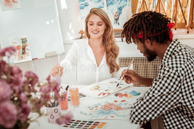 Ελκυστικός μοντέρνος δάσκαλος τέχνης που αισθάνεται τη χαρούμενη ζωγραφική με το σπουδαστή της στοκ φωτογραφία με δικαίωμα ελεύθερης χρήσης