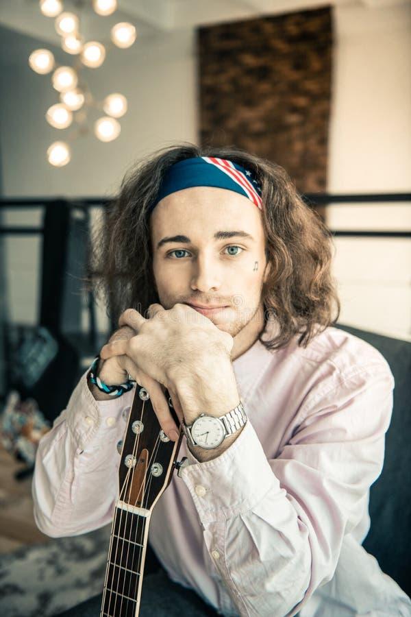 Ελκυστικός νέος μουσικός που φορά το ελαφρύ πουκάμισο και το ζωηρόχρωμο bandana στοκ εικόνες