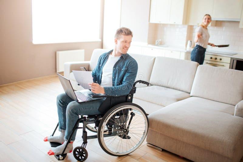 Ελκυστικός νέος σπουδαστής με το inclusiveness και ειδικές ανάγκες Κάθισμα στην καρέκλα και να ξανακοιτάξει Νέο μαγείρεμα γυναικώ στοκ εικόνα με δικαίωμα ελεύθερης χρήσης