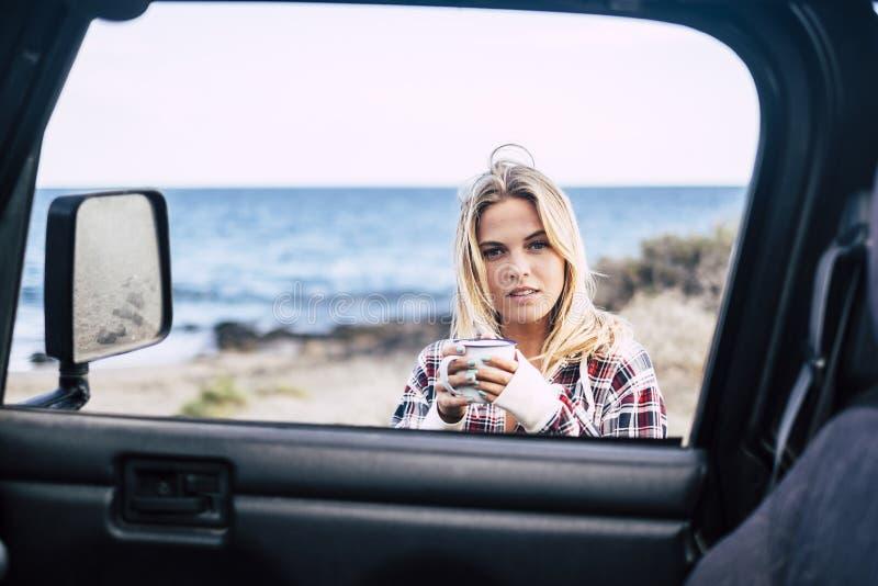 Ελκυστικός νέος χιλιετής ξανθός βγάζει ένα σπάσιμο έξω από την από το οδικό αυτοκίνητο ενώ ταξίδι και ανακαλύπτει τον κόσμο - hip στοκ φωτογραφία