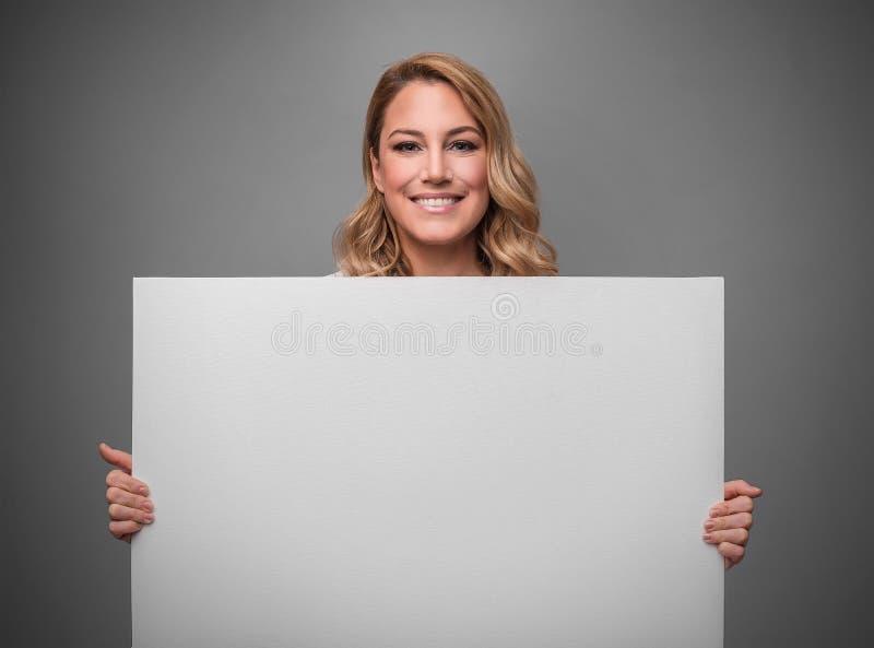 Ελκυστικός ξανθός κρατά την άσπρη κενή κενή αφίσα για το κείμενό σας ή την εικόνα σε ένα γκρίζο υπόβαθρο στοκ φωτογραφία με δικαίωμα ελεύθερης χρήσης