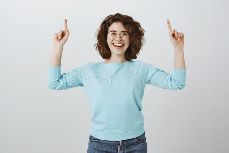 Ελκυστικός οδηγός μουσείων που παρουσιάζει τουρίστες γύρω Πορτρέτο της ευτυχούς χαρούμενης γυναίκας σπουδαστή στα γυαλιά, αίσθημα στοκ εικόνες