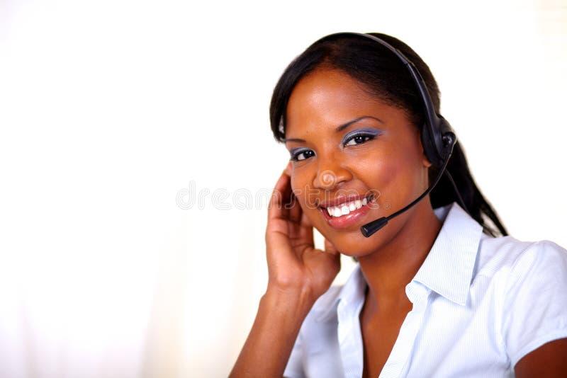 Ελκυστικός ρεσεψιονίστ που χαμογελά και που εξετάζει σας στοκ εικόνα με δικαίωμα ελεύθερης χρήσης