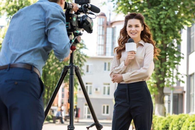 ελκυστικός χαμογελώντας θηλυκός δημοσιογράφος με το μικρόφωνο στοκ φωτογραφία