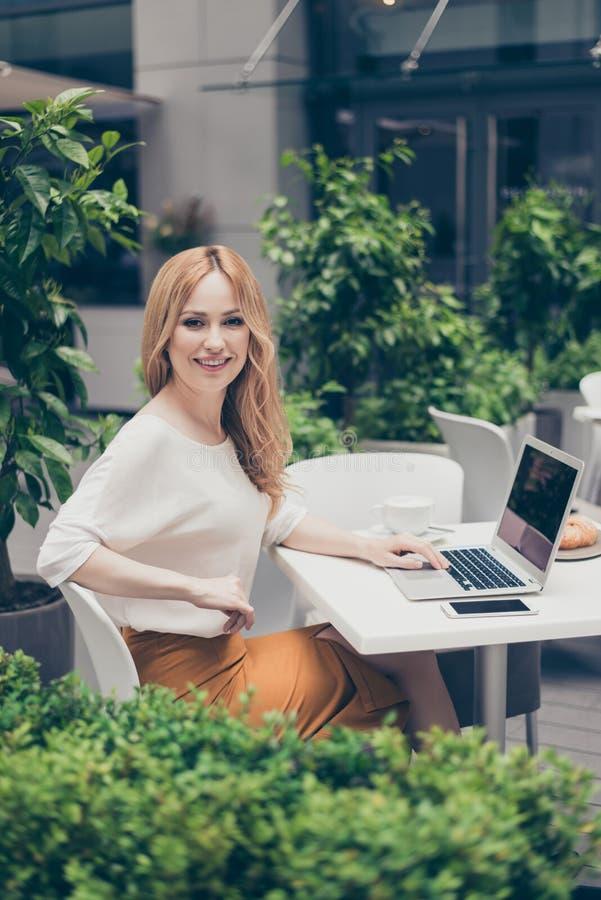 Ελκυστικός, όμορφος, κομψός διευθυντής που χρησιμοποιεί τη σύγχρονη εργασία συσκευών στοκ εικόνα