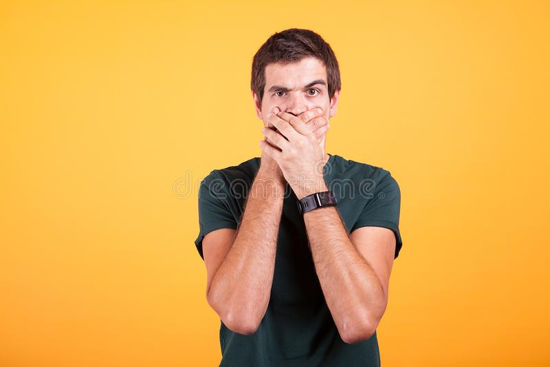 Ελκυστικό άτομο που καλύπτει το στόμα του σε κανένα σημάδι συζήτησης στο κίτρινο υπόβαθρο στοκ εικόνες με δικαίωμα ελεύθερης χρήσης