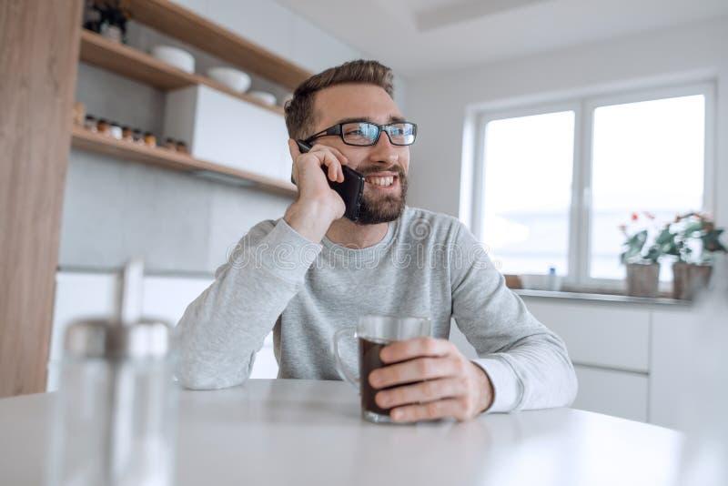 Ελκυστικό άτομο που μιλά στο smartphone του κατά τη διάρκεια του προγεύματος στοκ εικόνα με δικαίωμα ελεύθερης χρήσης