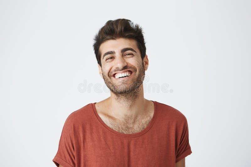 Ελκυστικό αξύριστο νέο σκοτεινός-ξεφλουδισμένο αρσενικό στην κόκκινη μπλούζα που χαμογελά ευρέως το γέλιο στην αστεία εικόνα στο  στοκ φωτογραφία με δικαίωμα ελεύθερης χρήσης